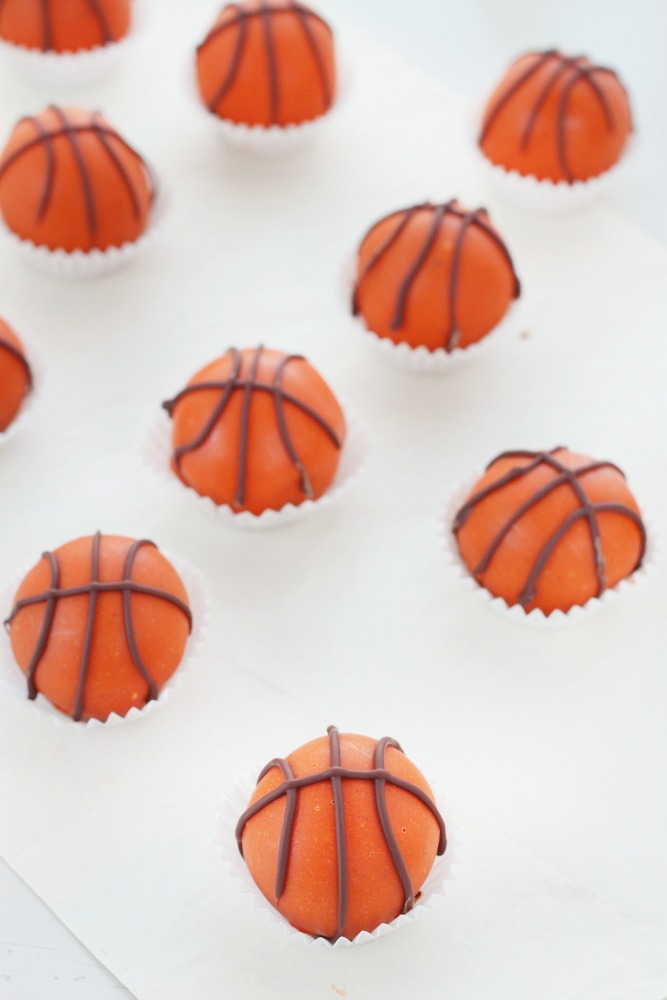 Score at your next basketball party with these hard to resist peanut butter and chocolate truffles shaped and decorated as mini basketballs!