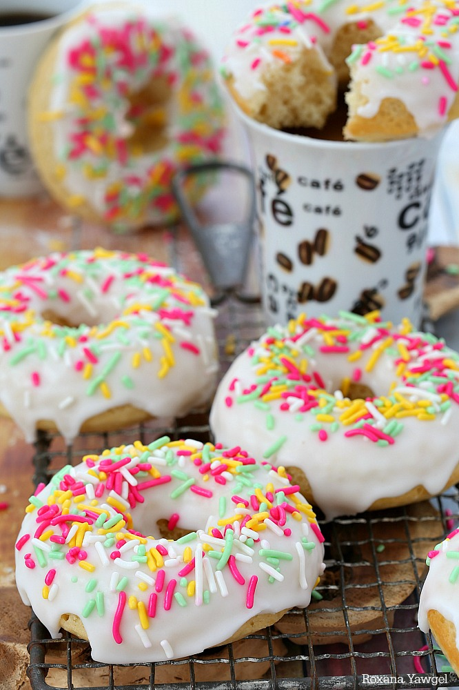 Soft and delicious baked donuts dipped in a thick vanilla glaze and topped with sprinkles, these glazed vanilla donuts are sure to brighten up your day!